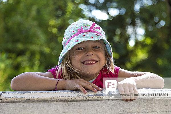 Portrait of little girl climbing on a wall