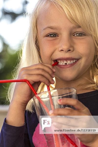 Kleines Mädchen trinkt Wasser mit Trinkhalm