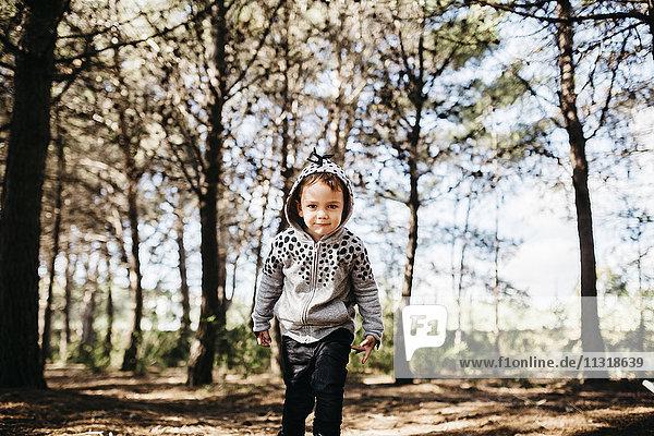 Portrait of little boy wearing hooded jacket in the woods