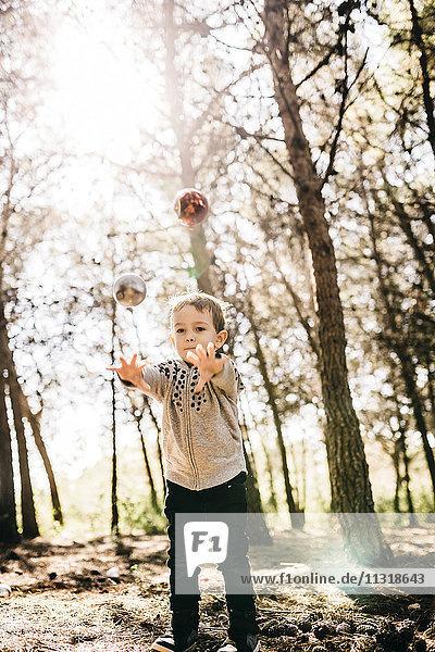 Kleiner Junge steht im Wald und wirft Weihnachtskugeln in die Luft.