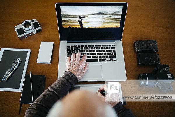 Senior-Fotograf mit Laptop  Draufsicht