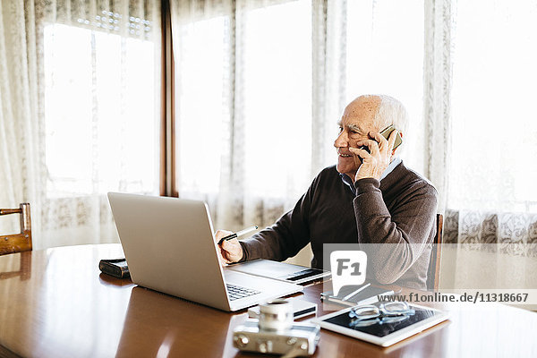 Senior-Fotograf am Telefon zu Hause