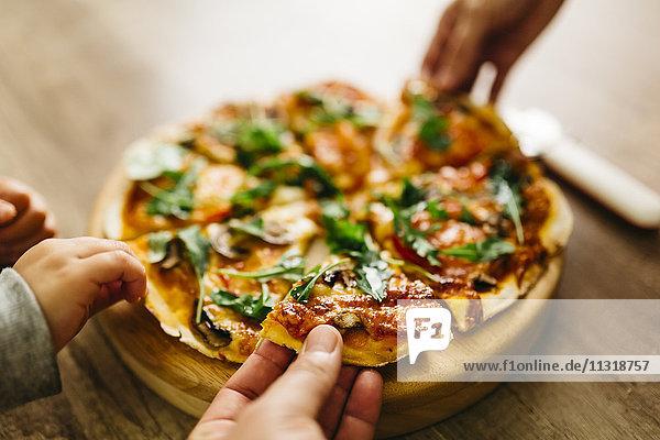 Hände beim Aufnehmen von Pizzascheiben
