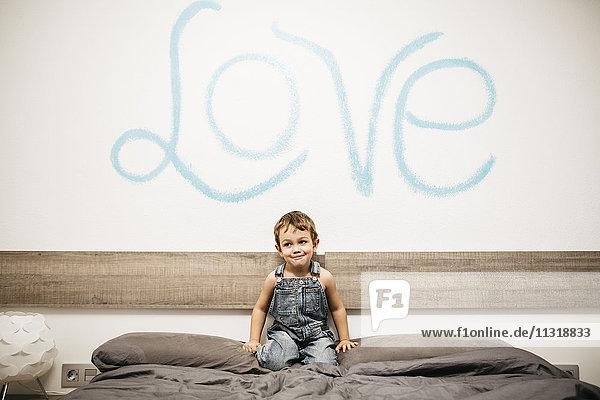Kleiner Junge  der auf dem Bett seiner Eltern hockt.