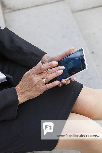 Woman's hand touching display of phablet
