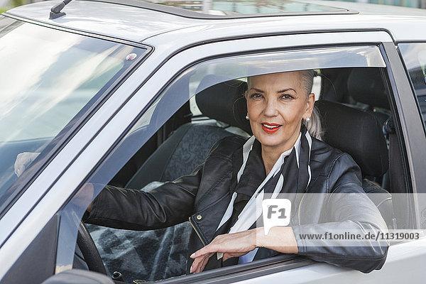 Porträt einer Geschäftsfrau  die aus dem Autofenster blickt