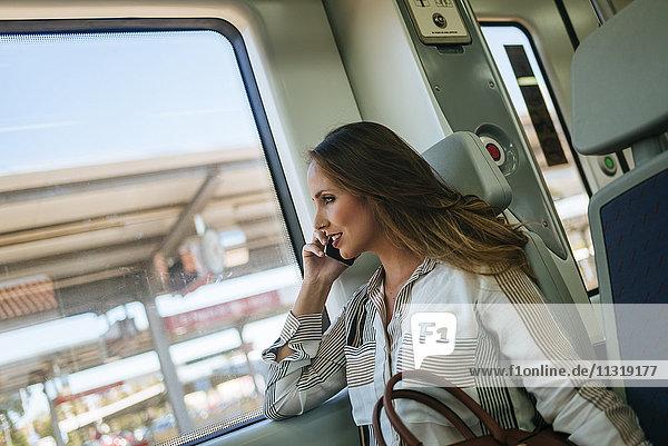 Frau im Zug  die mit dem Handy telefoniert