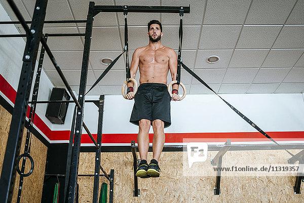 Mann macht Übungen an Ringen im Fitnessstudio