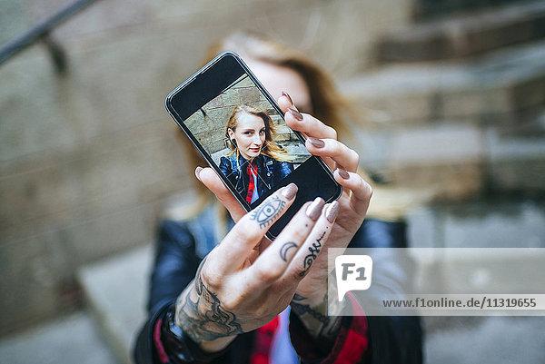 Tätowierte Frauenhände nehmen Selfie mit Smartphone  Nahaufnahme