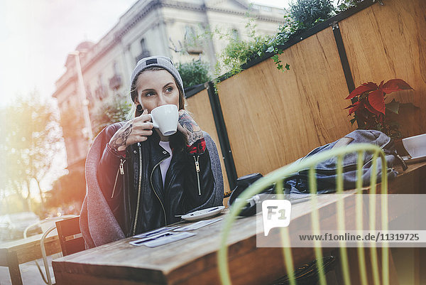 Young tattooed woman sitting in pavement cafe drinking coffee