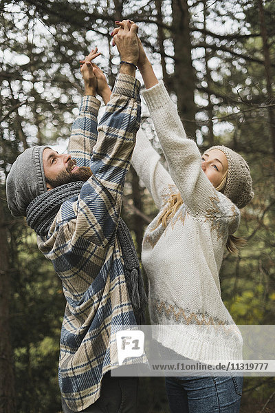 Happy young couple raising their arms together