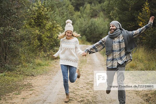 Glückliches junges Paar  das im Herbst auf dem Weg läuft