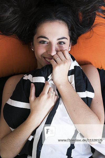 Schöne junge Frau im Bett liegend