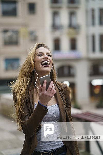 Glückliche junge Frau beim Musikhören mit Kopfhörer und Smartphone