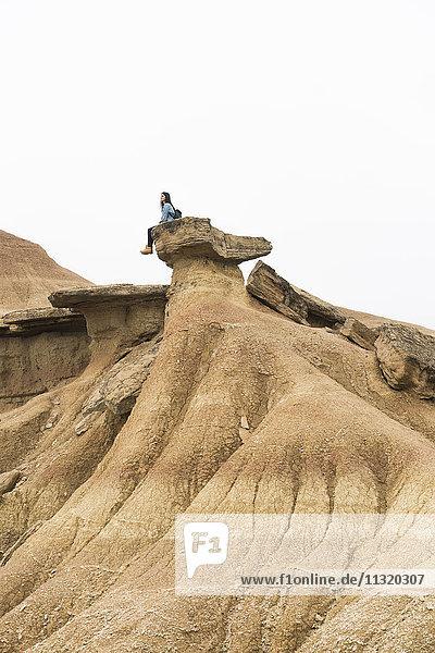Spanien  Navarra  Bardenas Reales  junge Frau auf einem Felsen im Naturpark sitzend  mit Blick auf die Aussicht