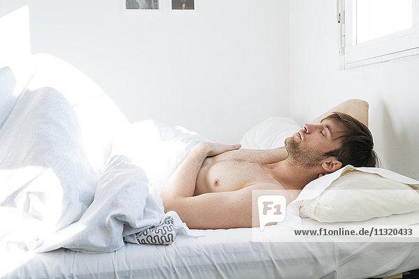 Mann entspannt im Bett