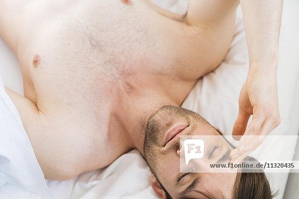 Junger Mann entspannt im Bett