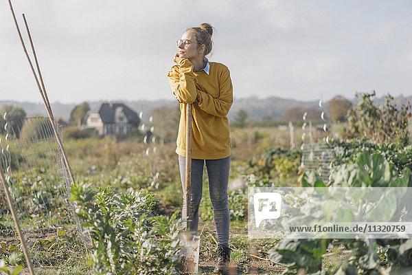 Junge Frau mit Spaten im Bauerngarten