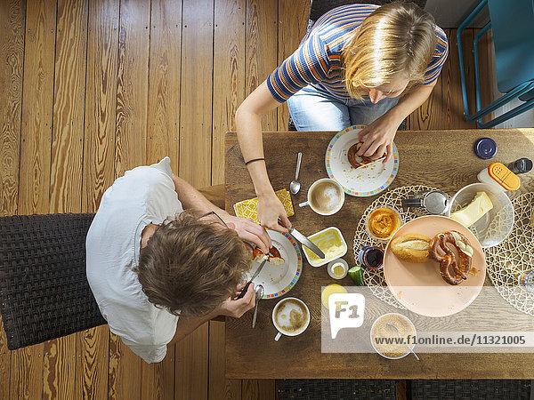 Junges Paar am Tisch sitzend  beim Frühstück  Blick nach oben