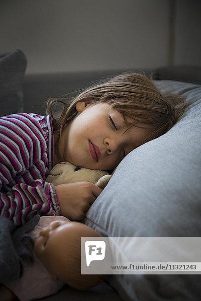 Porträt eines kleinen Mädchens,  das auf der Couch schläft.