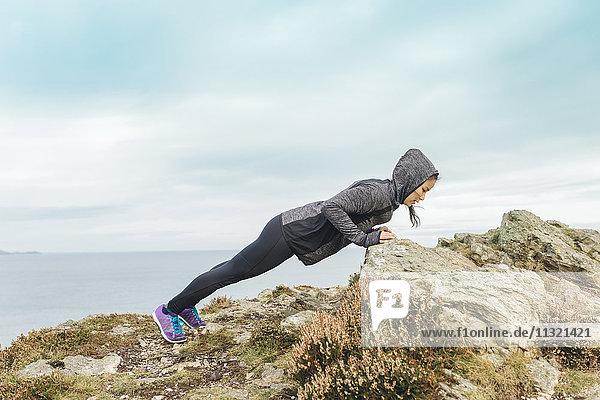 Irland  Howth  Frau beim Training an der Steilküste