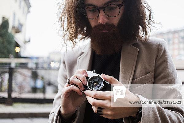 Stilvoller junger Mann im Freien mit Kamera