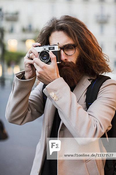 Stilvoller junger Mann im Freien  der mit einer altmodischen Kamera fotografiert.