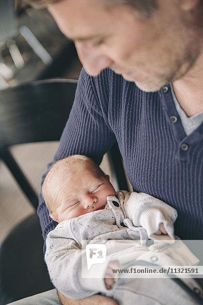 Der reife Vater hält sein schlafendes Baby.