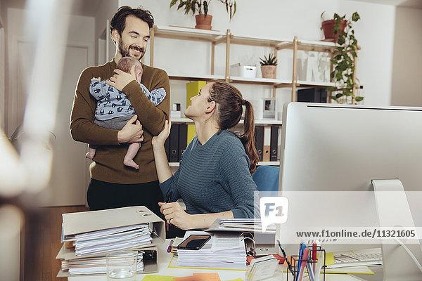 Lächelnde Mutter am Schreibtisch mit Blick auf Vater mit Baby im Home-Office