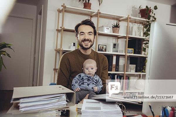 Porträt des lächelnden Vaters mit seinem Baby im Home Office