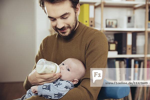 Vater füttert sein Baby zu Hause