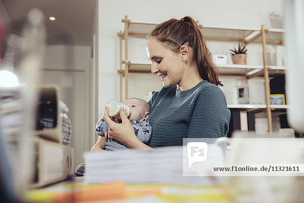 Woman feeding her baby in home office
