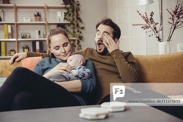 Müde Vater und Mutter sitzend mit Baby auf der Couch