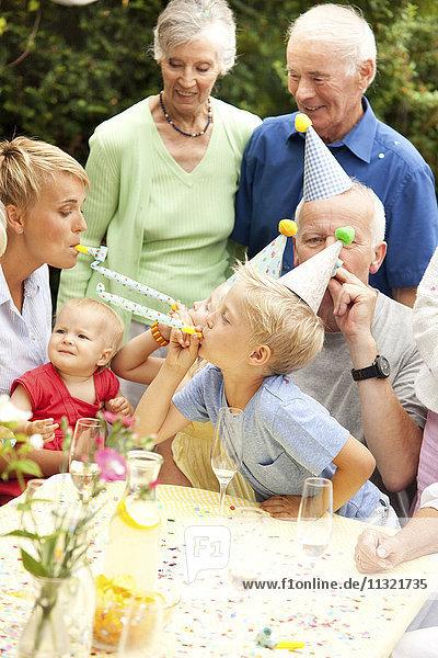 Erweiterte Familie und Freunde bei der Geburtstagsfeier im Garten