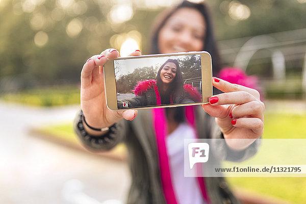 Junge Frau  die im Herbst einen Selfie in einem Park macht.