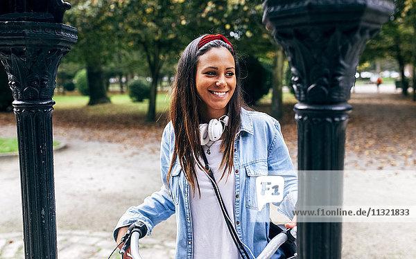 Porträt einer lächelnden jungen Frau mit Fahrrad im Park