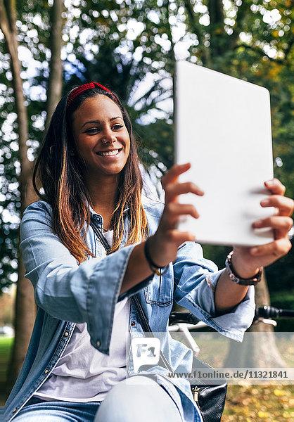 Lächelnde junge Frau  die einen Selfie mit einer Tablette im Park nimmt