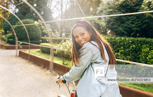 Lächelnde junge Frau beim Radfahren im Park