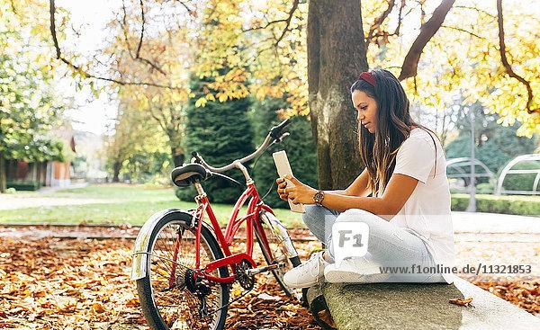 Junge Frau mit einer Tablette im Herbst im Park