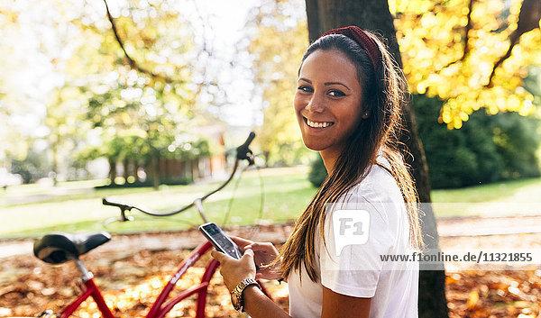 Porträt einer lächelnden jungen Frau in einem Park im Herbst