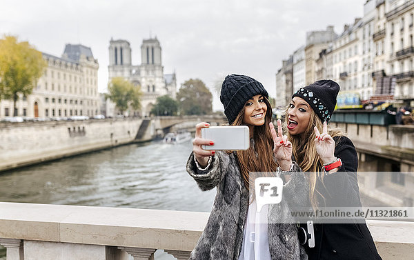 France  Paris  tourists taking selfie with cell phone
