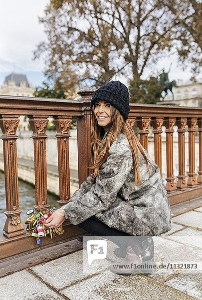 Frankreich  Paris  Porträt einer glücklichen jungen Frau  die ein Liebesschloss am Geländer einer Brücke befestigt.
