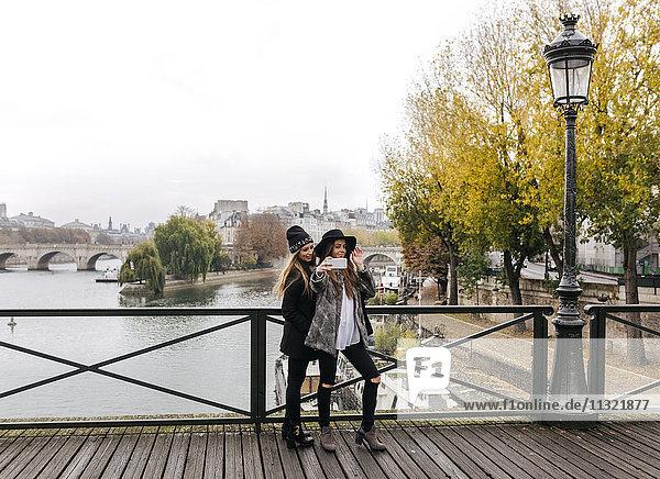 Paris  Frankreich  zwei junge Frauen  die Selfie auf einer Brücke nehmen.