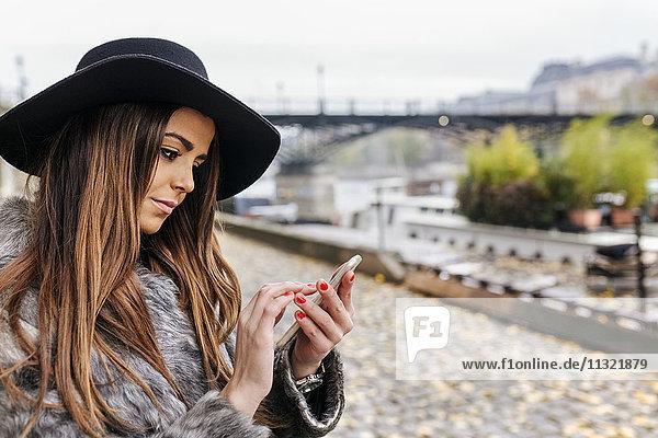 Frankreich  Paris  Portrait einer jungen Frau  die in der Nähe der Seine telefoniert.
