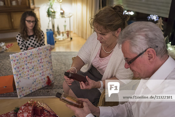 Schenken am Weihnachtsabend  Großeltern beim Betrachten von Flaschen