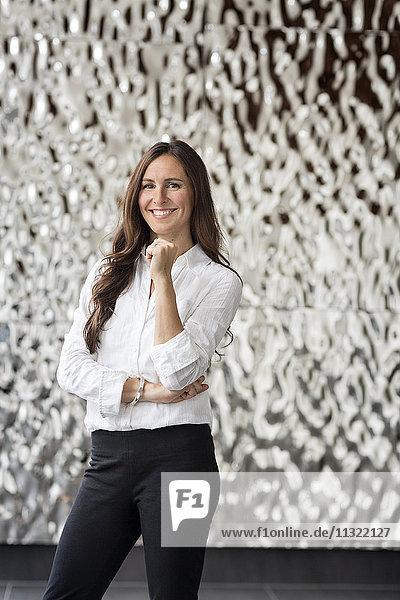 Porträt einer selbstbewussten Geschäftsfrau vor geriffelter Wand
