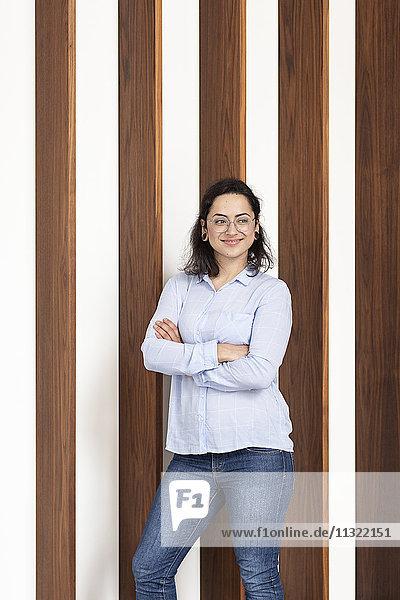 Lächelnde junge Frau vor der Holzwand