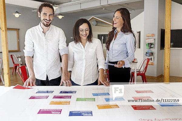 Drei glückliche Kollegen im modernen Büro