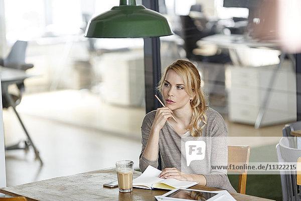 Frau im Büro mit Notebook-Denken