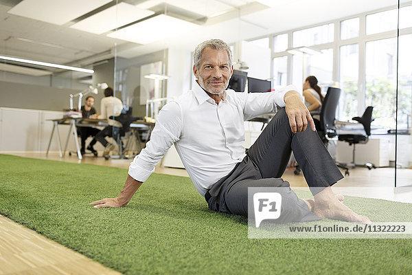 Lächelnder Geschäftsmann sitzt auf Teppich im Büro